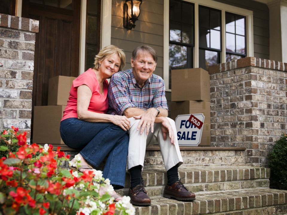 Couple sitting on steps of sold home.